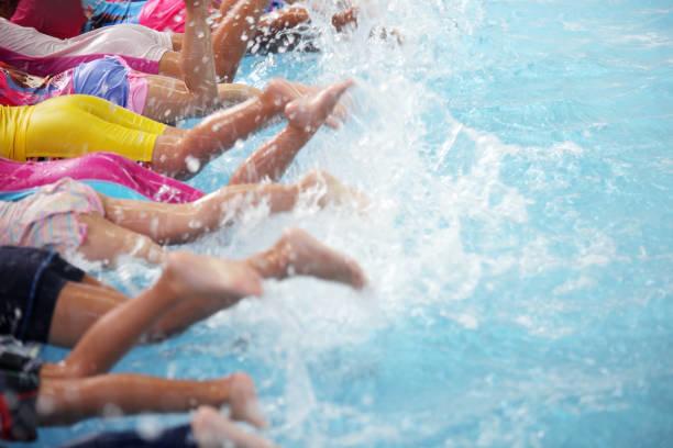 泳ぐことを学ぶスイミング プール クラスの子どもたちの...