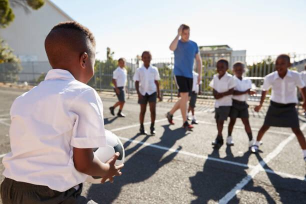 先生は子供たちに学校の校庭でサッカーを果たしています。