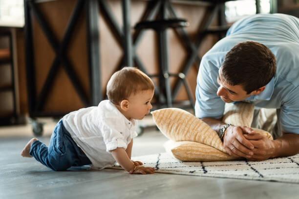 家で父親と一緒に過ごしながら這う小さな男の子。