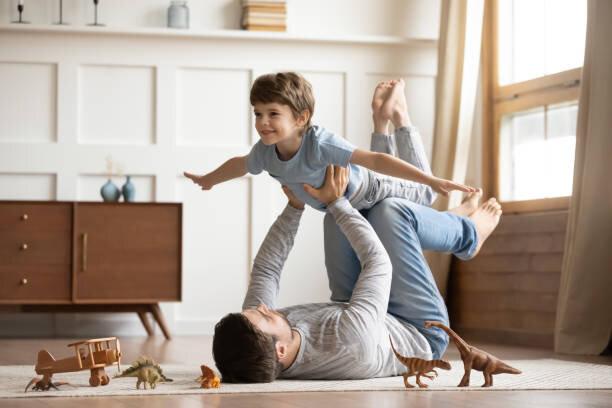 興奮した幸せな小さな息子を持ち上げる喜びに満ちた若者の父親。