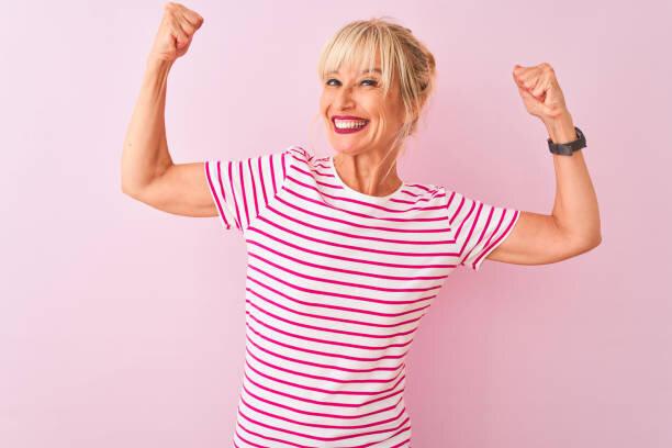 孤立したピンクの背景の上に立つストライプのTシャツを着...