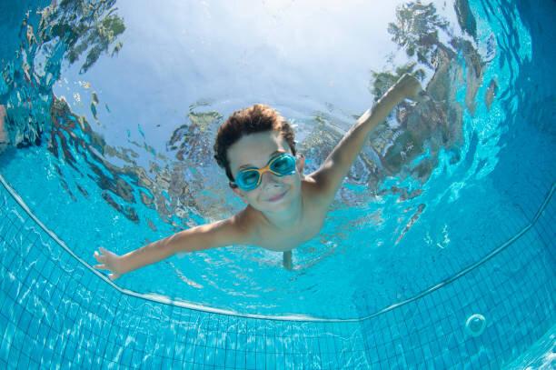 ゴーグルとスイミングプールで水中若い男の子の楽しみ