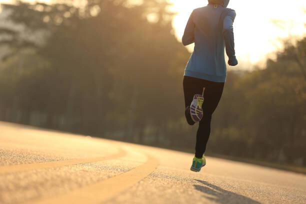 日の出の道を走る若いフィットネス女性ランナー