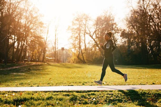 公園で走っている熱心なアフリカ系アメリカ人の女性アスリート。