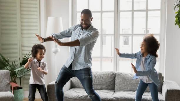 若いアフリカの民族の父親は、ダンスに小さな子供たちを教...