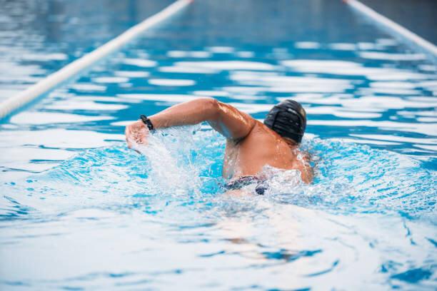 背中を泳ぐアスレチック・ヤング・マンがプールで這う。水...