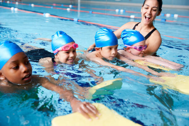 屋内プールで子供の水泳レッスンを与える水の女性コーチ