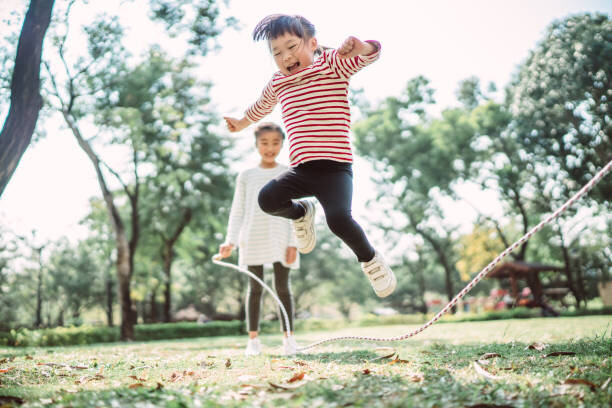Young family jumping rope j...