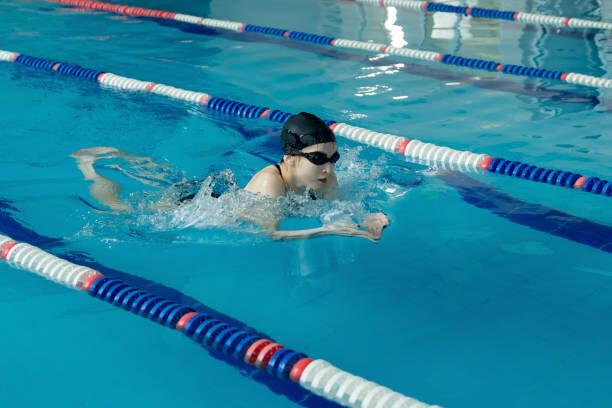 ゴーグルと青い水の屋内レース プールで平泳ぎのストロー...