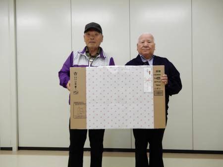 総合優勝に輝いた梅津さん(左)に記念品を手渡す三輪会長(右)