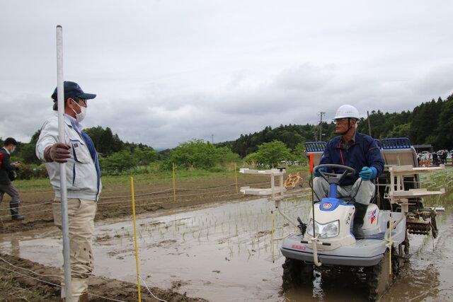 田植えを見守る木幡組合長(左)