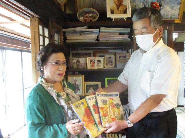 家計簿を見せ思い出を語る美喜子さん(左)と根本いわき地区本部長(右)
