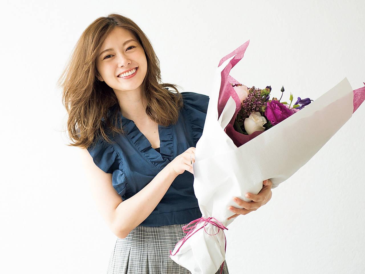 花を持って笑顔の白石麻衣