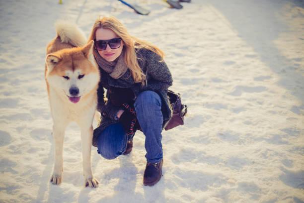 昔ながらの女性は彼女の犬に近いひざまずく
