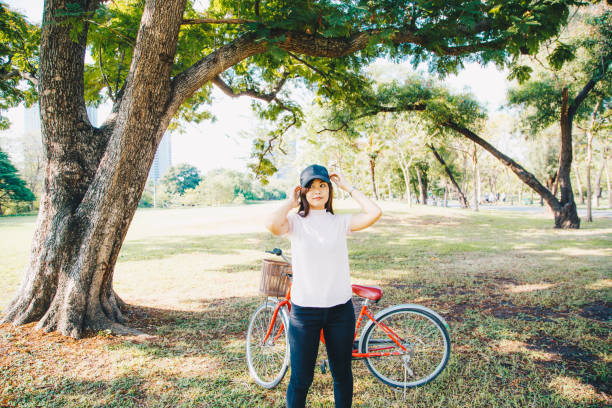 Full Length Of Woman With Bicycle Standing On Field By Trees
