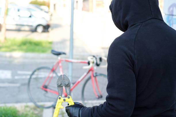 街の通りで自転車を盗む泥棒