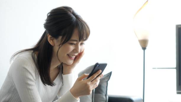 リビングルームでスマートフォンを使用して、魅力的なアジ...