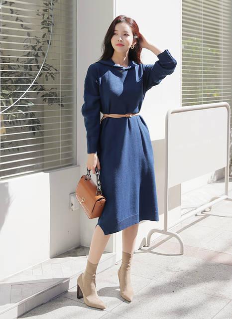 青のニットワンピを着て待つ女性