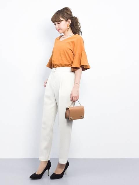 白のパンツとオレンジのトップスを使った春夏のオフィスカジュアルコーデ