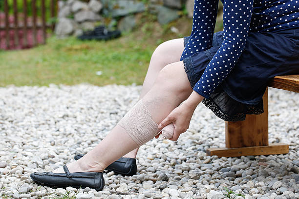 ベンチに座り脚をマッサージする女性