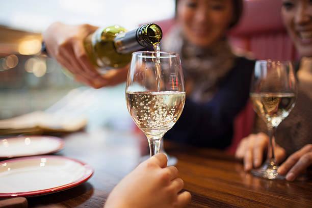 Woman pouring white wine, c...