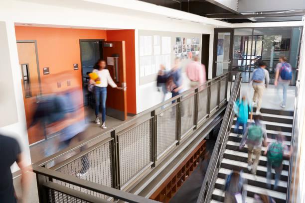 高校の廊下を休憩の間にぼやけている学生とスタッフ忙しい