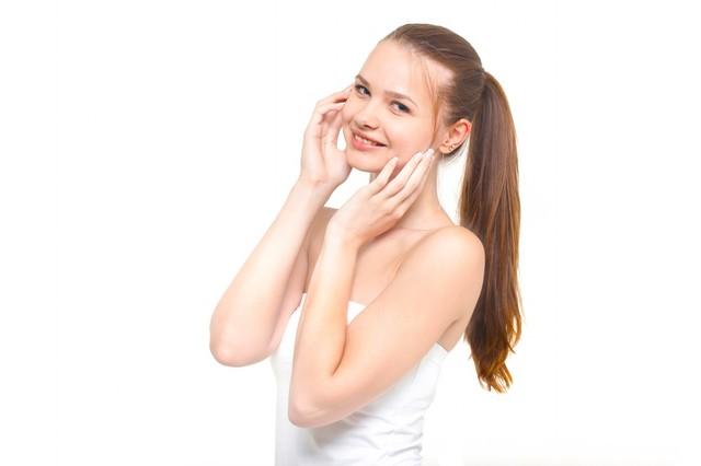 両手を頬に当てながら優しく微笑む横目線の女性|フリー写真素材・無料ダウンロード-ぱくたそ (20937)