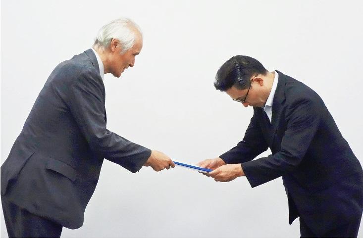 署名を受け取る佐藤守孝高齢者支援課長(右)