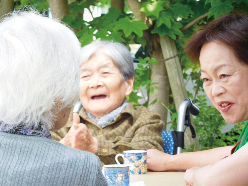 「喫茶の時間」利用者と談笑する小枝施設長(右)