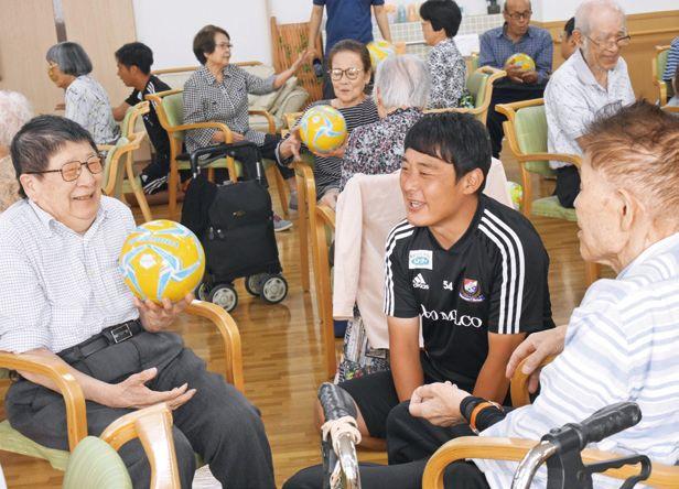 (写真1)キャッチボールをしな がら利用者とコーチの会話も弾む