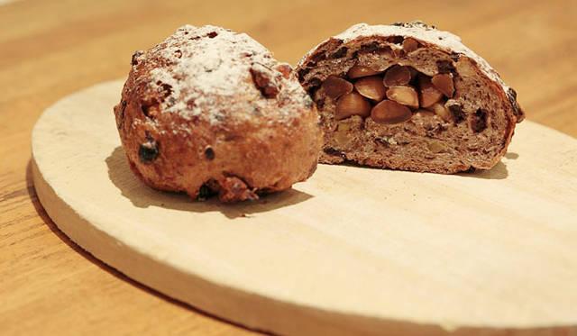 <strong>Loin montagne|ロワンモンターニュ</strong> 卵、牛乳、バター不使用。北海道産全粒粉にクルミ、ラム酒漬けのカレンツ、愛媛産いよかんピール入りの生地で、素焼きしたマカデミアナッツを包み込んで焼きあげたパン「森の木の実」。焼きあがり予定時間9:00 1個170円