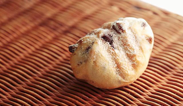 <strong>PANADERIA TIGRE|パナデリア ティグレ</strong> 天然酵母のぶどうパンの生地に、クリームチーズとフレッシュブルーベリーを包み込んで焼いた「ブルドーム」は、三角形のユニークなかたち。焼きあがり予定時間 12:00  1個200円