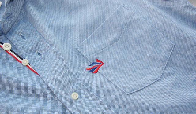 <strong>flaph × BARNEYS NEYORK</strong> 胸ポケットに刺繍されたブランドロゴはユニオンジャックをアレンジしたもの。フラフのアイデンティティをポップに物語る。