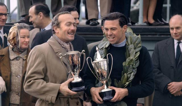 <strong>Colin Chapman and Jim Clark |コーリン・チャップマン&ジム・クラーク</strong><br />1964年のグッドウッド・フェスティバルにて ロータス創始者のチャップマン(左)と、その彼に才能を見出された天才F1レーサーのジム・クラーク(右)