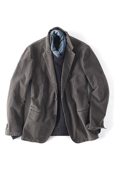 """<strong><div class=""""tText"""">More Rugged Style</div> 味出しジャケットで<br /> 「大人のラギッド」を表現 </strong><br /><br />  もう一方の、ラギッドな着こなしのバリエーションがこちら。ウォッシュ加工のジャケットは「こなれた感じ」を漂わせつつも、崩し過ぎない雰囲気を保持してくれる便利なアイテム。一着持っておくと非常に重宝するはず。そして秋らしいグレーのVネックニットの襟元にはストールを。シンプルなトップスコーディネートのアクセントとして効果的である。  <br /><br /><br /> ジャケット5万1450円、ニット2万4150円、ストール1万500円"""
