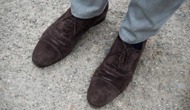 """<p class=""""PtitleD"""">エレガントなスエード靴</p> <p class=""""Ptext"""">この靴選びもまた、この方の個性である。ストレートチップ(キャップトウ)をセレクトする場合、たいていは黒だ。もし茶としても濃いものだろう。というのもビジネスシューズとして最もドレッシーな型とされているので、通常は表革を選ぶのである。それをあえてのスエード素材というチョイス。やはりひとクセある人物である。"""