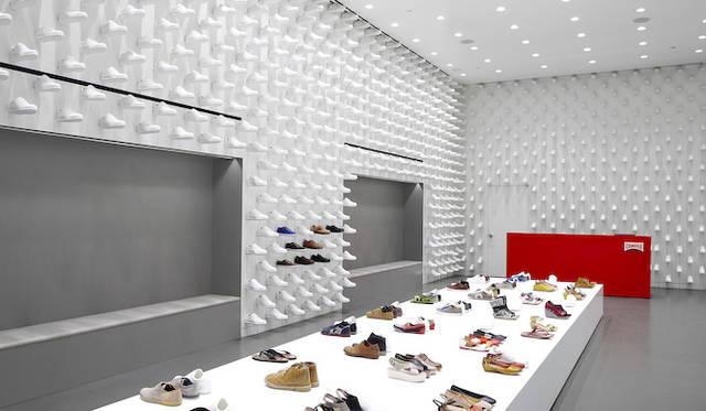 佐藤オオキ氏デザインのCAMPER ニューヨーク店<br /> 「空中を自由に歩き回るクツ」をテーマに、大阪、パリ、サンフランシスコ、モスクワなどで展開された 第一弾の小型店舗用コンセプトに引き続き、新たに第二弾として開発された大型店舗用コンセプト。 高い天井高を活用するべく、カンペールの定番商品である「Pelotas」というクツを白い樹脂で成型し、それを使って空間を覆うことで、まるで「倉庫」のような整然とした雰囲気とボリューム感を空間に与えることにした。これらのクツは窓から入る外光に呼応するように陰影を壁面に生み出し、立体的なテクスチャーを空間にもたらす