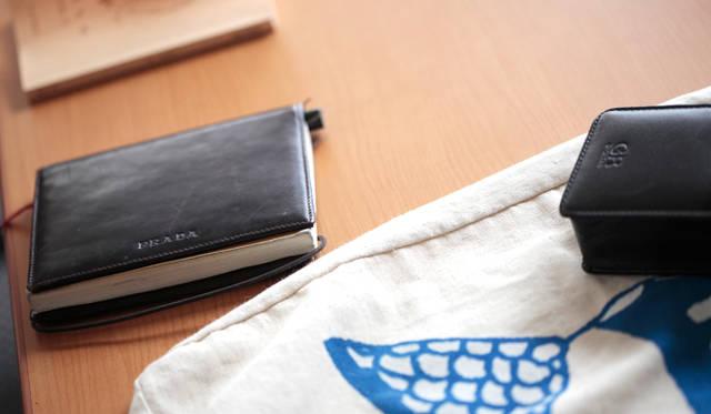 文庫本のカバーをかけた無印良品の「再生紙ノート・無地 A6」(左)と、リコーのコンパクトデジタルカメラ「GR」。中央のサブバッグは、旅先で使用するもの