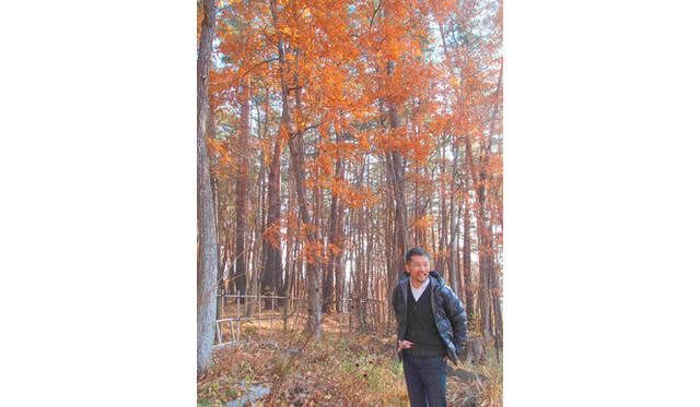 <strong>特集|「パーマカルチャーデザイン」を暮らしのなかに</strong> 紅葉が美しい広葉樹の林の前で。林の奥には小麦畑があるという