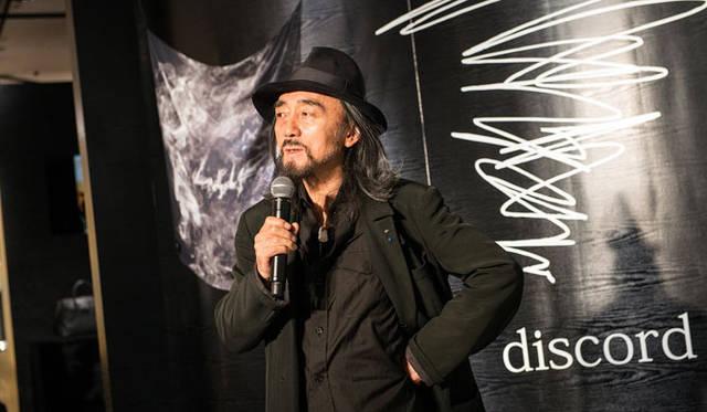 discordのイメージを山本耀司氏自らが表現したブランドロゴの前で