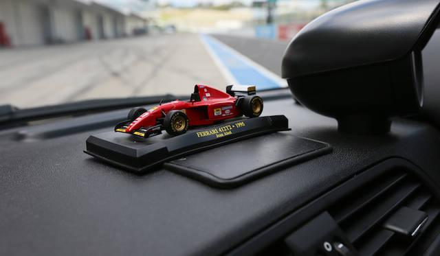 ダッシュボード上には、檜井選手がしばしば国内で操縦を任されている往年のフェラーリF1マシン、1995年シーズン用412T2の1/43ミニチュアカーが鎮座している