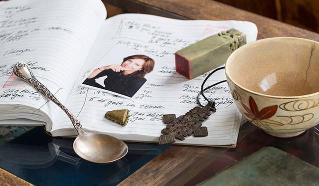 スミスさんのお茶作りを支える7つ道具。いま「スティーブンスミスティーメーカー」で出している商品はすべて、この道具を使って生み出したものだそうだ。手前から時計回りにスプーン、重石、夫人の写真、レシピノート、ハンコ、お碗、首飾り