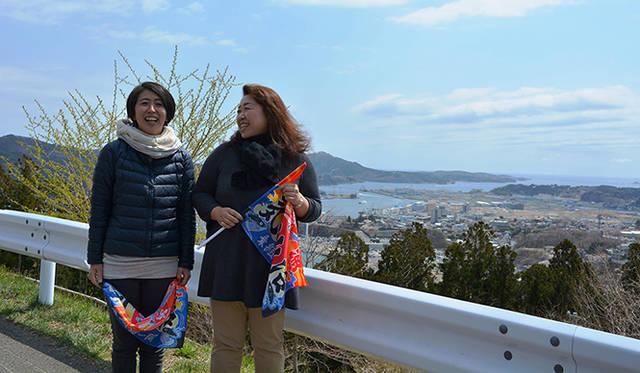 私たちを出迎えるためのミニ大漁旗を手にする斉藤和枝さんと小野寺紀子さん