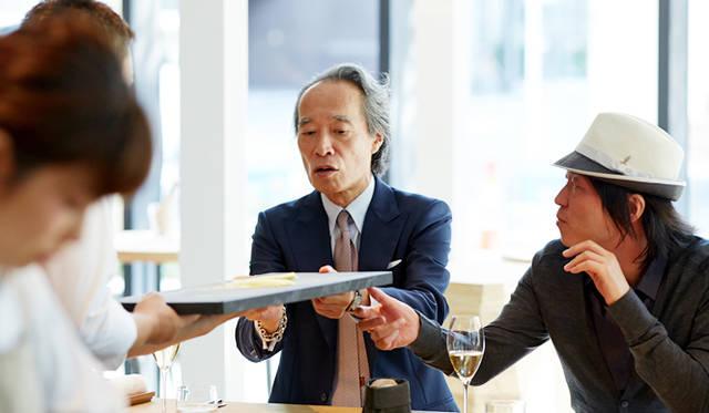 """一品目を終わると、目の前の""""黒い""""まな板に興味を示した川上氏と大住。「フランスでは、使う材料によってまな板の色を変えるのが一般的なんですよ」と小林シェフ。客席とキッチンの距離が近いため、こうしたさりげない会話が自然とはじまる"""