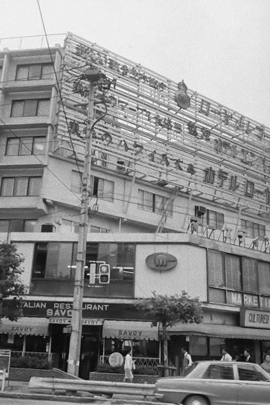 <strong>写真集アプリ「野上眞宏のSNAPSHOT DIARY」</strong> 1971年10月 セントラルアパートの明治通り側の外観写真。原宿の表参道と明治通りの角、今は「東急プラザ 表参道原宿」のある所にセントラルアパートはあった。コープオリンピア、山手教会とともに、70年代初頭の原宿の象徴だった。地下鉄もまだなく竹下通りもただの裏通りだったし、原宿は人通りの少ない静かな街だった。セントラルアパートのきちんとした写真が現存していないようなので、この写真をもっとまじめに撮っておけばよかったなぁと反省! &#169; Mike Nogami