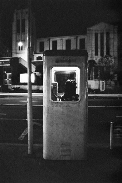 <strong>写真集アプリ「野上眞宏のSNAPSHOT DIARY」</strong> 1971年11月 原宿、表参道。夜の街を一人で歩くのは好きだ。手で耳をふさぐと夜の都会の美しさが際だってくる。夜の写真はたくさん撮った。当時でも珍しくなりつつあった旧型電話ボックス。背景は山手教会で、細野が結婚式を挙げた場所。今はラフォーレ原宿が、この跡地に建っている。 &#169; Mike Nogami