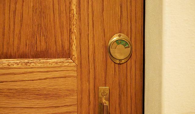 化粧室のドアに付いている真鍮製の鍵。半円状の小窓にグラフのように情報が現れる明快なデザイン