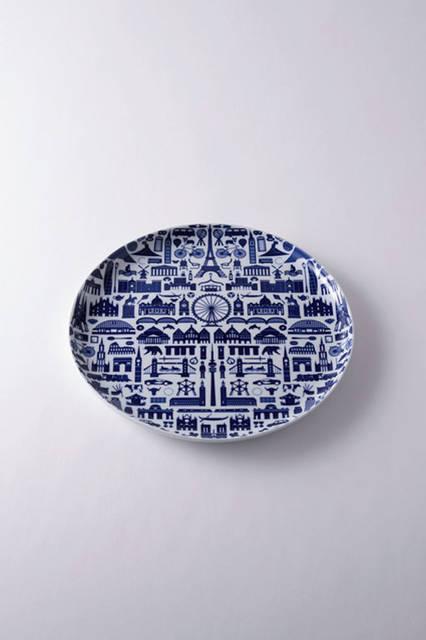 """キハラの絵付け皿で「ヨーロッパ・アイコン」の銘がついている。キハラは昭和30年に設立された、磁器商社で、自らを産地の職人とクリエイターなどをつなぐ""""ハブ""""として自任している。職人たちの手仕事へのこだわりは、半端がなく、このプレートも、パリをイメージする絵付けの柄がユーモラスにして見事で、日本の陶磁器らしいブルーの深みがシックである。<br /><br />  <strong>キハラ</strong><br /> Tel. 0955-43-2325<br /> <a href=""""http://e-kihara.co.jp"""" target=""""_blank"""">http://e-kihara.co.jp</a>"""