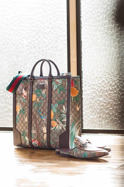 花々の間をハチドリや蝶が飛び回るコレクション「Gucci Tian」。コンテンポラリーでありながらシグネチャーウェブ、GGパターン、ホースビットなどアイコニックなモチーフがちりばめられている。シューズの左右でプリントが異なるのも魅力のひとつ。 <br><br> バッグ[W37×H39.5×D12cm]23万5440円〈阪急メンズ大阪2階〉〈阪急メンズ東京1階〉、シューズ9万2880円/グッチ〈阪急メンズ大阪2階〉〈阪急メンズ東京2階〉