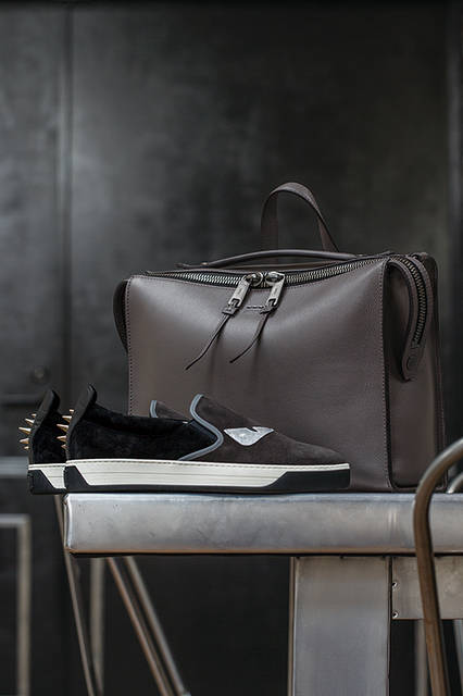シンプルでクリーンなデザインに、ビッグジップやふたつのハンドルといった個性的な要素をミックスしたバッグは、機能性も抜群。モノトーンのスエード素材のシューズには、アイコニックな「バッグバグス」がフェンディらしい遊び心を添えている。 <br><br>  バッグ[W36×H27×D15cm]42万120円、シューズ10万440円/フェンディ 〈阪急メンズ大阪3階〉〈阪急メンズ東京3階〉